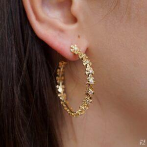Argola com detalhes de flores e zircônias folheada a ouro 18k